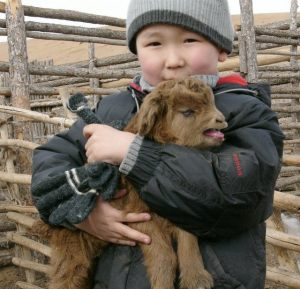 A young boy in Kyrgyzstan holds his family's goat